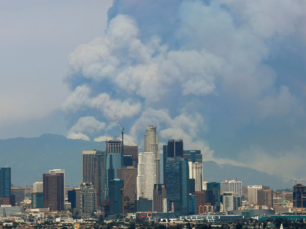 PHOTO: Smoke from two fires burning in the Angeles National Forest rises with the downtown skyline in the foreground in Los Angeles, June 20, 2016.