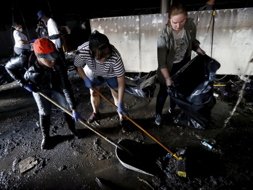 PHOTO: Members of the community clean up a recently looted and burned CVS store amid concerns about the buildings stability in Baltimore, April 28, 2015.