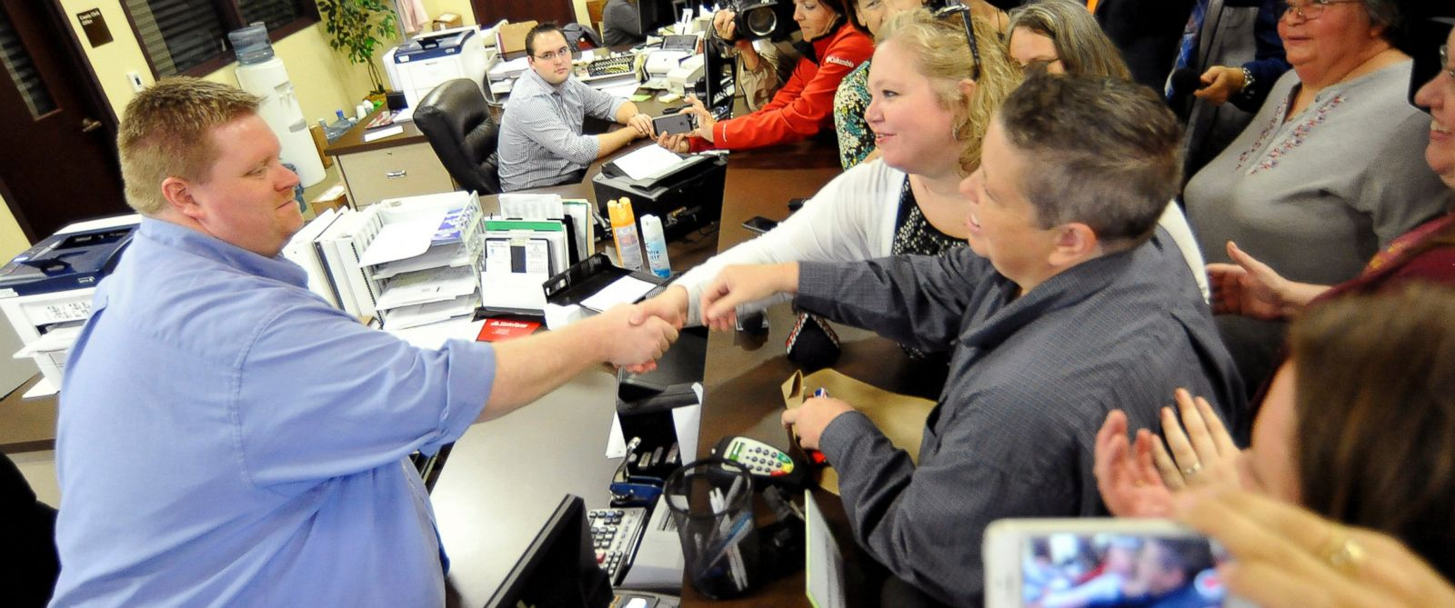 PHOTO: Deputy clerk Brian Mason, left, shakes hands with Carmen and Shannon Wampler-Collins after issuing them a marriage license at Rowan County Clerks Office in Morehead, Kentucky, Sept.14, 2015.