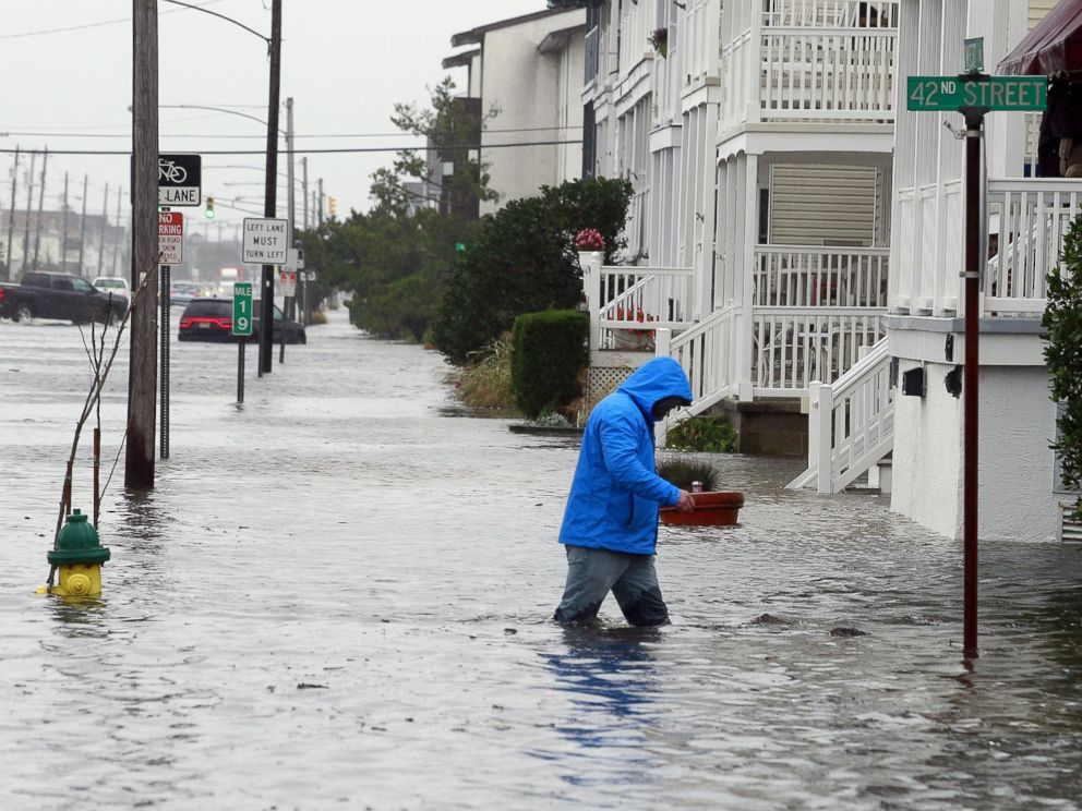 PHOTO: A man walks through knee-deep water along a flooded West Avenue as a nor-easter comes on shore in Ocean City, N.J., Oct. 2, 2015.