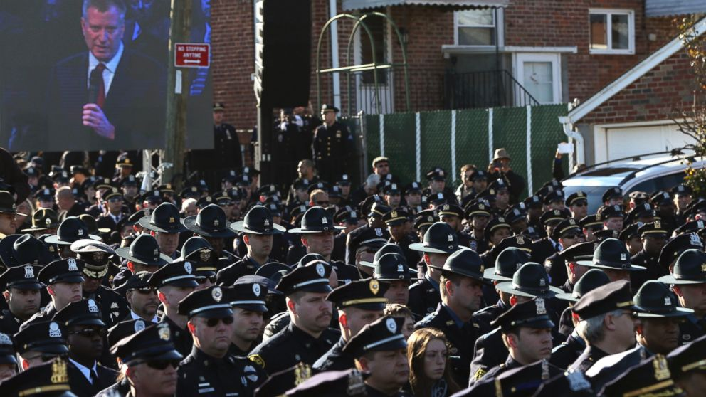 PHOTO: Law enforcement officers turn their backs on a video monitor as New York City Mayor Bill de Blasio speaks during the funeral of slain New York Police Department officer Rafael Ramos in the Queens borough of New York on Dec. 27, 2014.