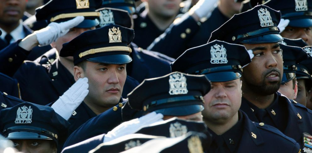 PHOTO: Police salute during the playing of the U.S. National Anthem outside the Christ Tabernacle Church at the start of the funeral service for slain New York Police Department officer Rafael Ramos in the Queens borough of New York, Dec. 27, 2014.