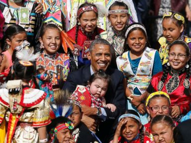 PHOTO: Barack Obama holds a baby as he poses with children at the Cannon Ball Flag Day Celebration at the Cannon Ball Powwow Grounds on the Standing Rock Sioux Reservation in North Dakota, June 13, 2014.