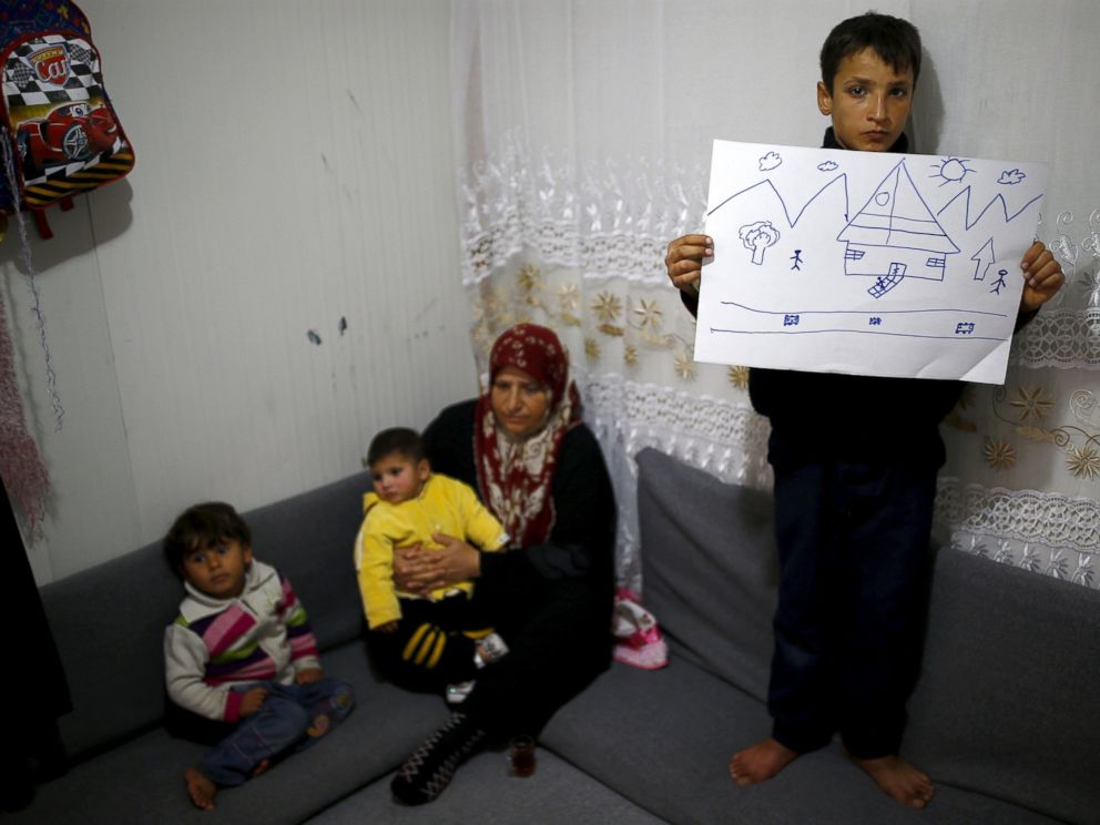 PHOTO: Syrian refugee Ahmet Cemal, 12, shows a drawing of home as his mother and his two brothers sit next to him in their tent in Nizip refugee camp in Gaziantep province, Turkey, Dec. 13, 2015.