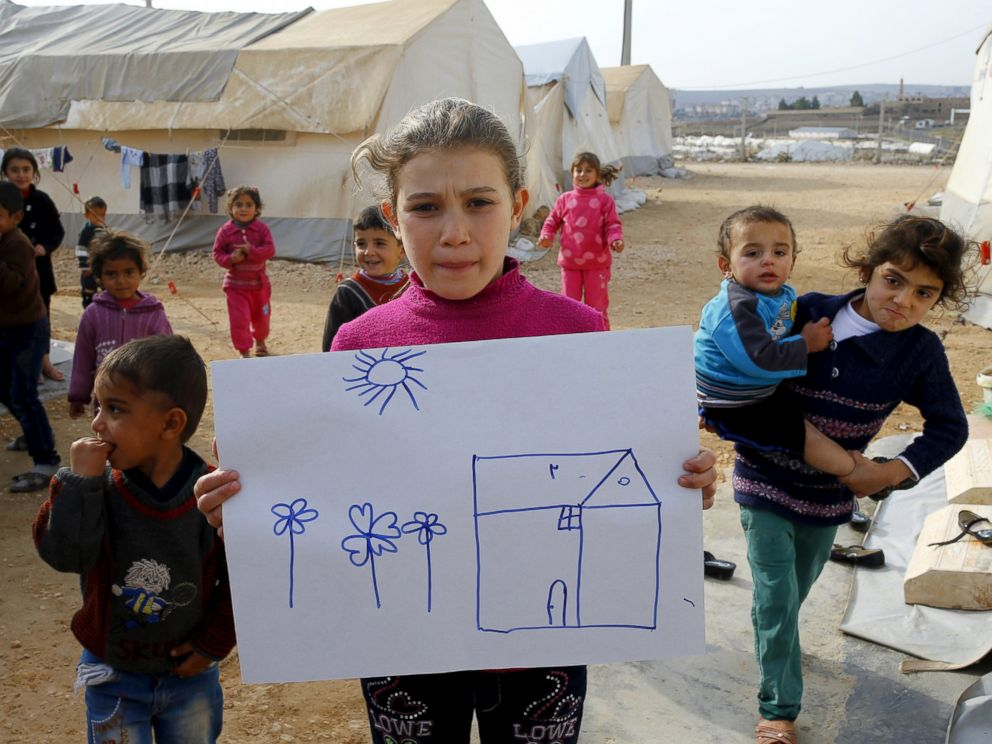 PHOTO: Syrian refugee Rahaf Hasan, 10, poses as she holds a drawing of her home in Syria in Midyat refugee camp in Mardin province, Turkey, Dec. 14, 2015.