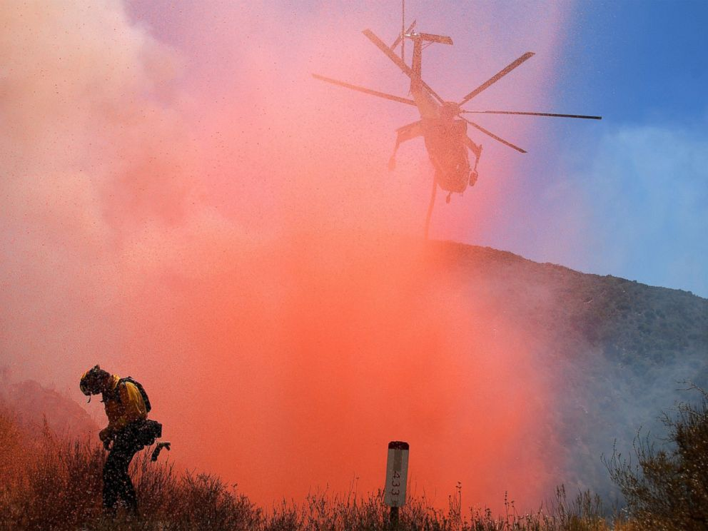 PHOTO: A fire fighter is sprayed with retardant as a helicopter makes a drop as emergency workers continue to battle fire in the Angeles National Forest near Los Angeles, California, July 25, 2016.