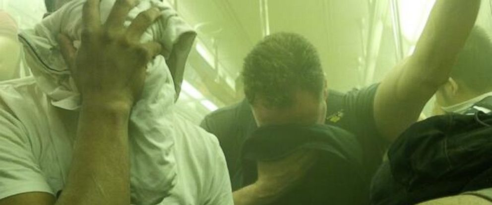 PHOTO: Passengers on New York Citys No. 7 train cover their faces as smoke fills the subway cars, June 2, 2014.