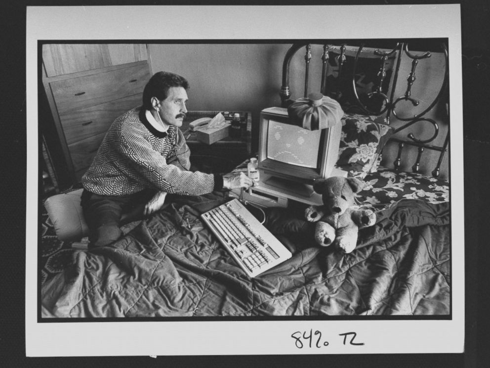 PHOTO: Computer analyst John McAfee holding stethoscope to IBM type computer sitting on bed w. ice bag on top, illustrating computer virus which McAfee is able to eradicate; at home.
