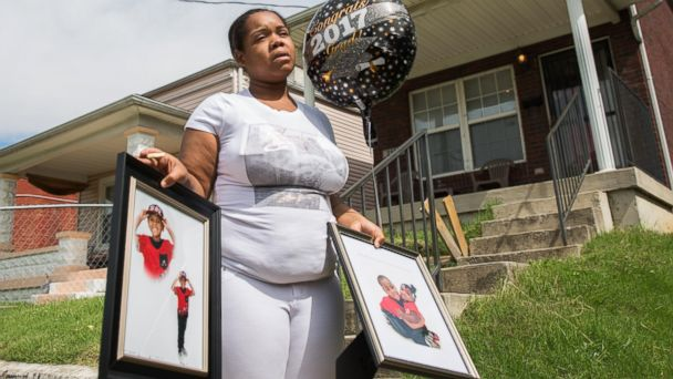 PHOTO: A May 22, 2017 photo shows Micheshia Norment holding photos of her son, Dequante Hobbs Jr., 7, who was shot by a stray bullet through the window while he was eating a snack at the dinner table in Louiville, Ky.