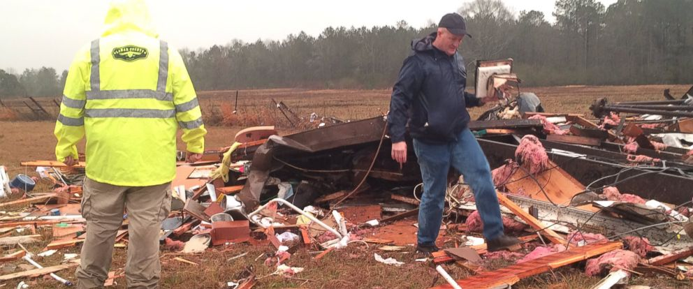 PHOTO: Family members pick up the pieces of a destroyed home at 166 Sones Road in Lamar County, Miss.