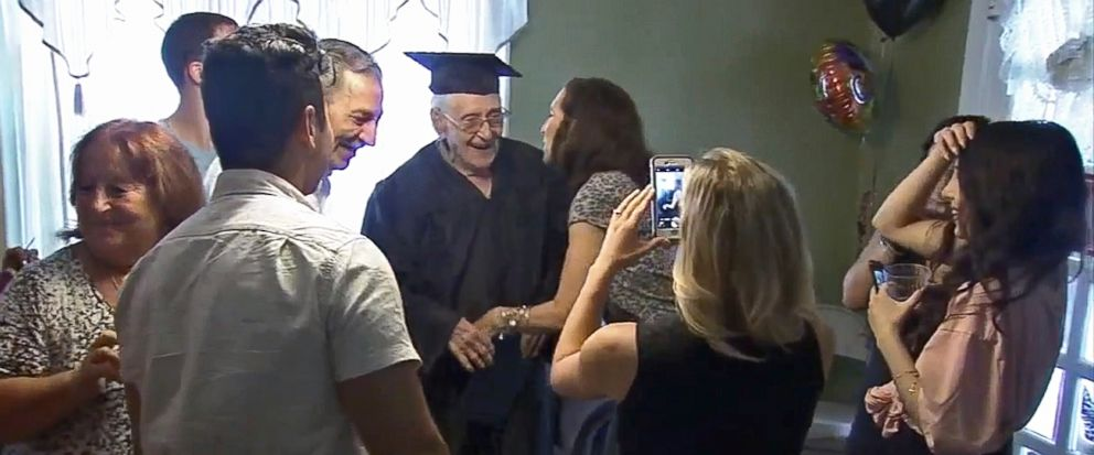 In this image from video provided by WPVI, Charles Leuzzi, center, a 97-year-old World War II veteran, is congratulated by friends and relatives after receiving an honorary high school diploma from the School District of Philadelphia on Sunday, July