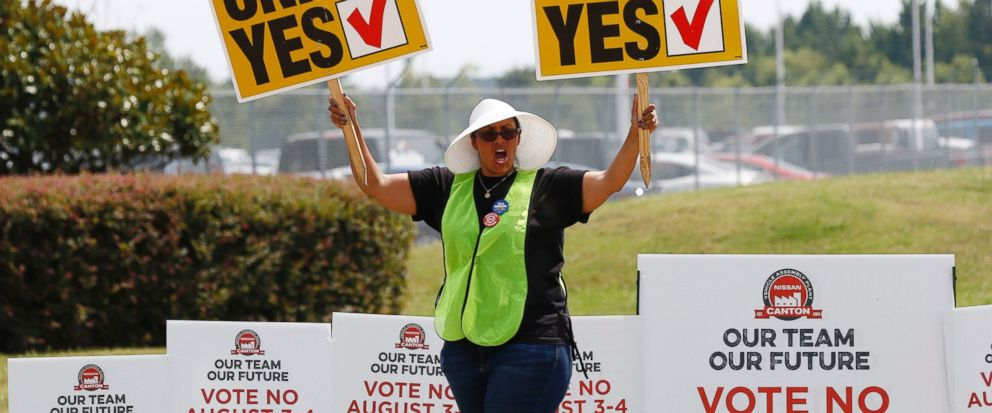 A UAW supporter sings as she tries to beat the hot sun outside an employee vehicle entrance at the Nissan vehicle assembly plant in Canton, Miss., Friday, Aug. 4, 2017. Union members set up informational lines outside employee entrances at the plant