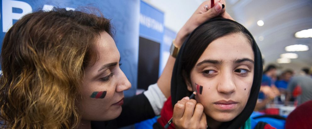 Afghanistan team member Somaya Faryuqi, right, has the flag of Afghanistan drawn on her cheek prior to the opening ceremony for the FIRST Global Challenge 2017, in Washington, Sunday, July 16, 2017. They will be competing against entrants from more t