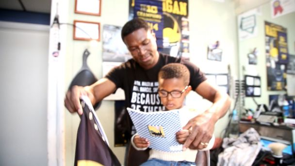 PHOTO: Jamal Martin reads as barber Alex Fuller tends to his hair. The Fuller Cut barbershop in Ypsilanti, Michigan, has been offering the Read to a Barber program for a year now.