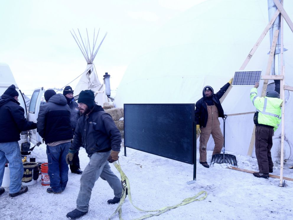 PHOTO: Terry Spoonhunter (second from right) and Silas Red Cloud (right) hold up a solar panel at the Oceti Sakowin Camp on the Standing Rock Reservation in Cannon Ball, North Dakota, Dec. 21, 2016.