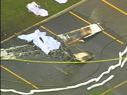 Picture of plane crash in parking lot.