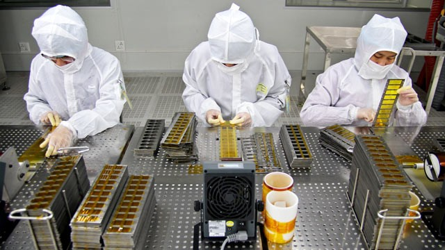 "PHOTO: In designated ""clean"" areas, employees will have to don anti-static ""bunny-suits."" These three workers are assembling the camera module for Apple's iPad in a factory in China."