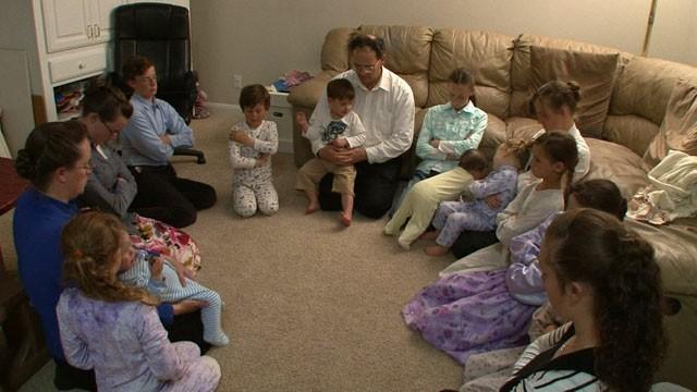 PHOTO: Michael Cawley avec certains de ses épouses et plusieurs de ses enfants prient lors d'un récent dimanche soir.