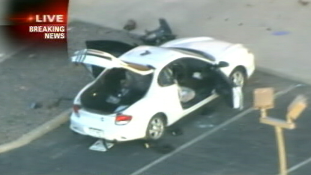 PHOTO: Police search the car of suspect, James Holmes, 24, of Aurora, who was caught by