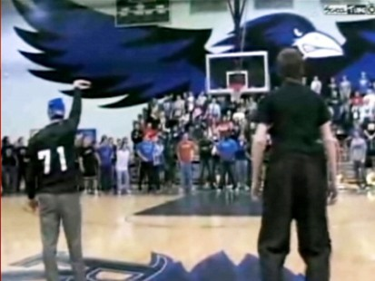 VIDEO: A blindfolded basketball coach sinks a half-court shot as part of a team bet.