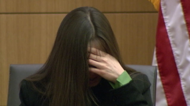 PHOTO: Jodi Arias hides behind her hands and hair while on the stand during her trial, Feb. 12, 2013.