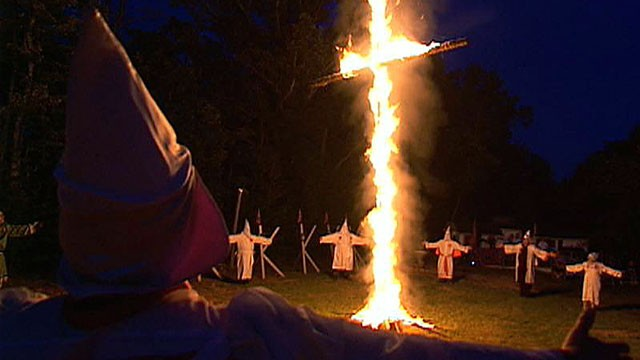 "PHOTO: Ku Klux Klan members burn a cross during a ""cross lighting"" outside Tupelo, Miss., in September 2012."