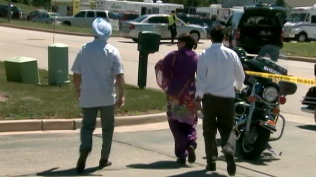 Bystanders flee the scene, as police investigate a shooting at the Sikh Temple of Wisconsin in Oak Creek, WI on Aug. 5, 2012.