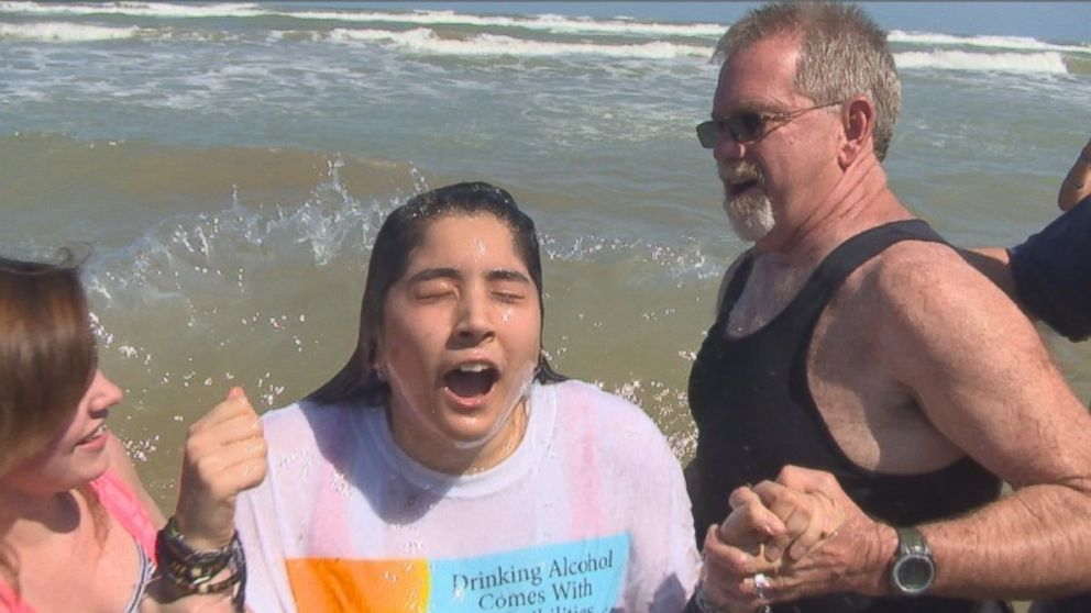 "PHOTO: A Christian ministry called ""Beach Reach"" heads to South Padre Island, Texas, each year to talk to spring breakers about God. Seen here is a young ministry member being baptized in the waves."