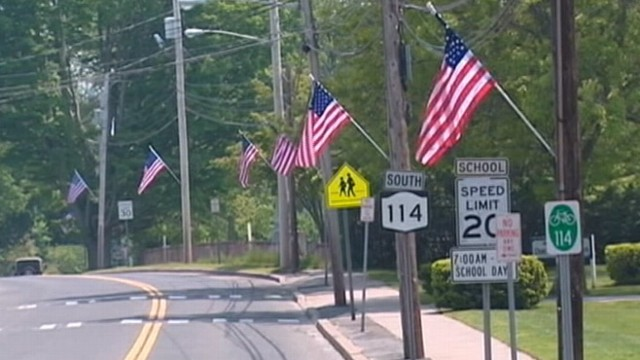 VIDEO: Community honoring fallen soldier is charged for hanging flags on utility poles.