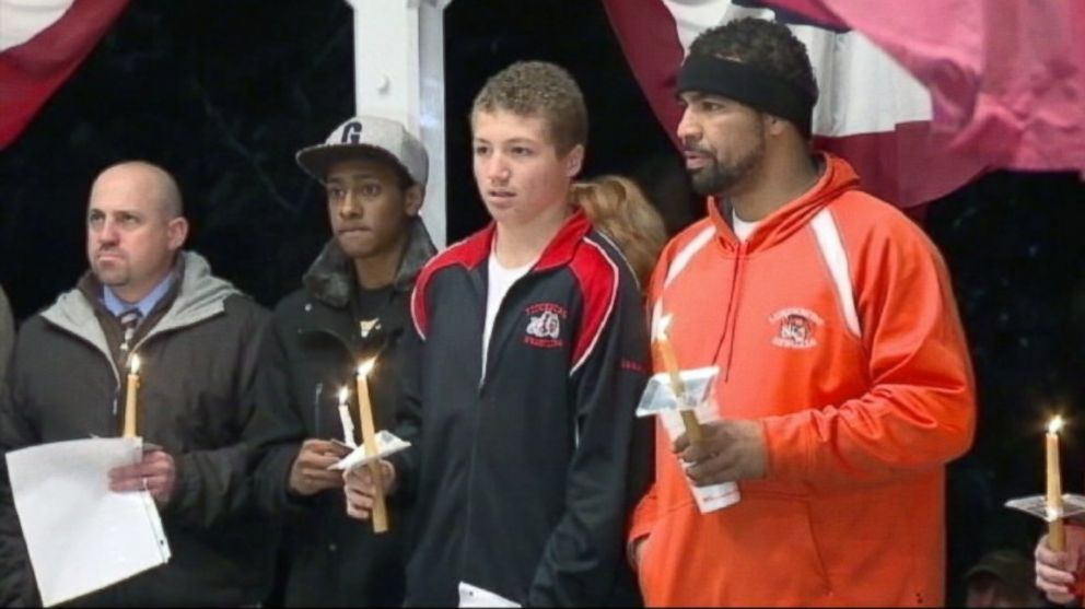 PHOTO: Lunenburg High School football player Isaac Phillips, second from right, is shown during a candlelight vigil in his honor.