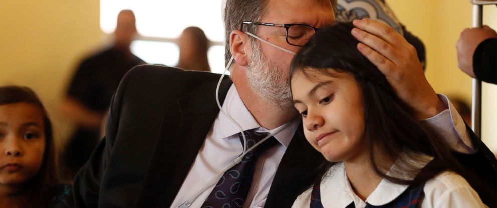 PHOTO: Dean Bortell, front left, kisses his 11-year-old daughter, Alexis, she waits to testify during a House committee hearing, March 6, 2017, in Denver.