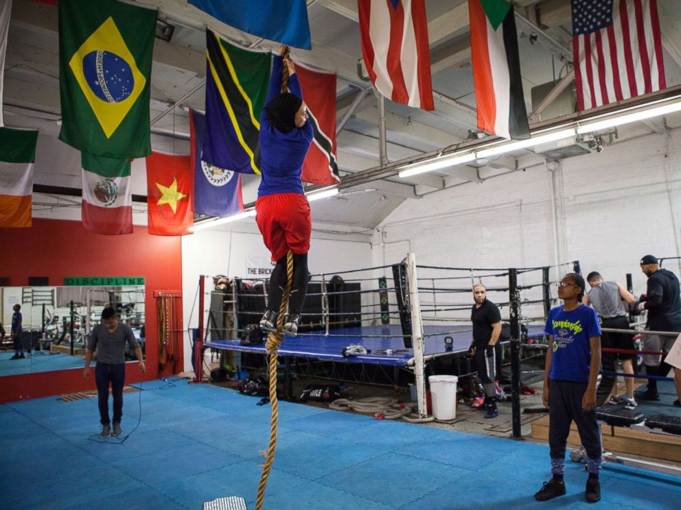 PHOTO: Amaiya Zafar attempts to climb the rope and touch the ceiling at Circle of Discipline boxing gym in Minneapolis.