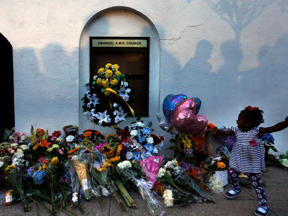 PHOTO: Mourners pass by a make-shift memorial on the sidewalk in front of the Emanuel AME Church following a shooting by Dylann Roof in Charleston, S.C., June 18, 2015.