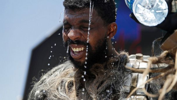 PHOTO: Xaviere Coleman, wearing a Wookiee costume, pours water over his head to cool off, June 20, 2017, in Las Vegas. The city hit 117 degrees, tying the record.