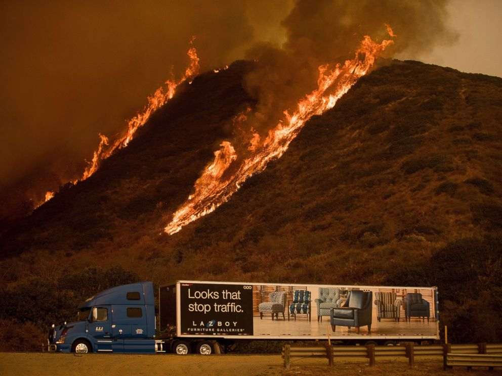 Flames from the Thomas fire burn above a truck on Highway 101 north of Ventura, Calif., on Wednesday, Dec. 6, 2017.