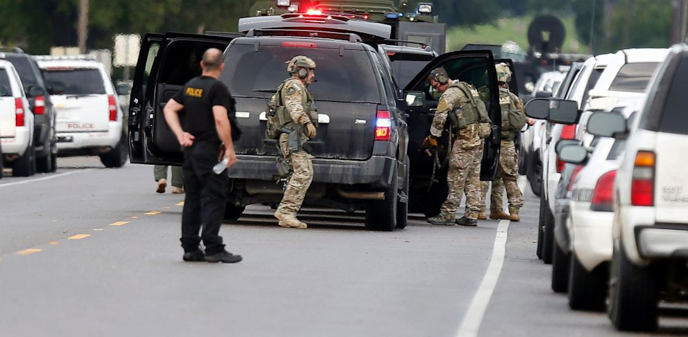 PHOTO: Louisiana state, federal and local law enforcement gather along La. Highway 128 outside a Tensas State Bank branch during a hostage situation in St. Joseph, La., Tuesday, Aug. 13, 2013.