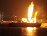 PHOTO: Fire burns aboard two fuel barges along the Mobile River after explosions sent three workers to the hospital Wednesday April 24, 2013.