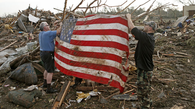 PHOTO: Clark Gardner, at left, and another man place an American flag on debris in a neighborhood off of Telephone Road in Moore, Okla., after a tornado moved through the area on Monday, May 20, 2013.