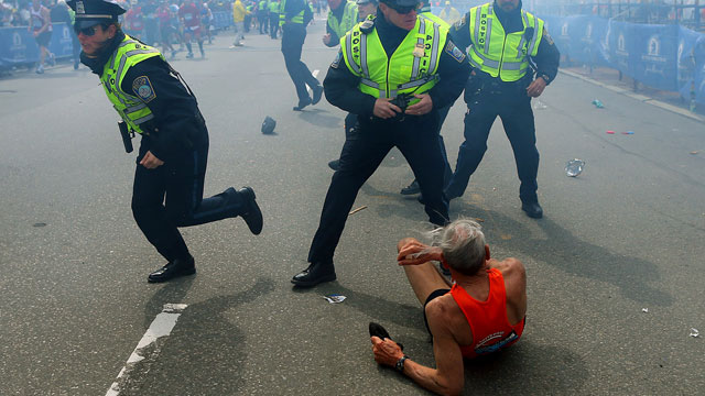 PHOTO: Bill Iffrig, 78, lies on the ground as police officers react to a second explosion at the finish line of the Boston Marathon in Boston, Monday, April 15, 2013.