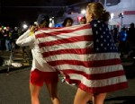 PHOTO: Taylor Richard, center, of Belmont, Mass., and Alyssa Kohler, 17, of Cambridge, Mass., wrap themselves in the American Flag in Watertown, Mass., April 19, 2013.