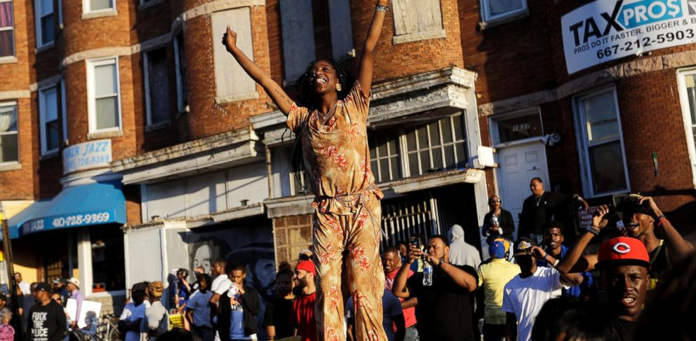 PHOTO: A woman stands on a car during a dance party in the street the day after charges were announced against the police officers involved in Freddie Grays death, Saturday, May 2, 2015, in Baltimore.