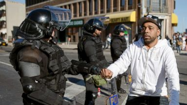 PHOTO: A man on a bicycle greets Maryland State Troopers, April 28, 2015, in the aftermath of protests following Mondays funeral for Freddie Gray, who died in police custody.