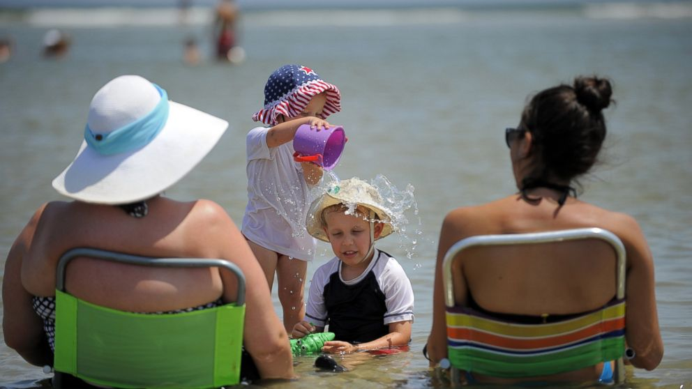 PHOTO: Lauren Rhyner, 1, dumps a bucket of water on her 4-year-old brother Jackson Rhyners head while the family cools off in a shallow tidal pool, Aug. 23, 2014, on Tybee Island, Ga.