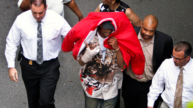 PHOTO: Sean Benschop, center, with red jacket over his head, walks with investigators as he arrives at the Philadelphia Police Departments Central Detectives Division, Saturday June 8, 2013, in Center City Philadelphia.