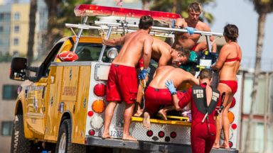 PHOTO: Lifeguards assist a person who was in the water and apparently struck by lightening Sunday July 27, 2014 in Los Angeles.