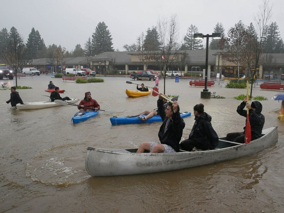 PHOTO: People use kayaks and a canoe to make their way around a flooded parking lot at a shopping center in Healdsburg, Calif., Dec. 11, 2014.