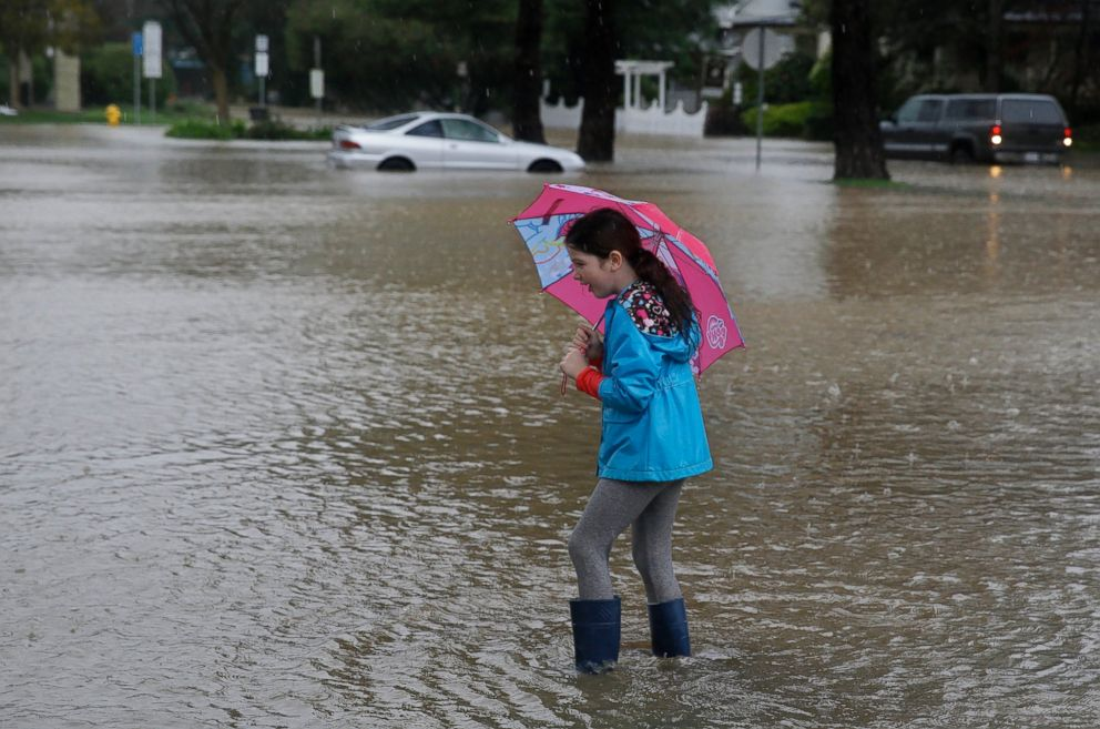 PHOTO: Hailey Thistle, 8, walks into a flooded parking lot at a shopping center in Healdsburg, Calif., Dec. 11, 2014.