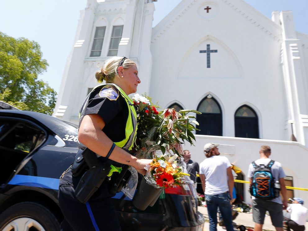 PHOTO: Charleston police officer T. Graves carries flowers, June 18, 2015 to a make-shift memorial in front of the Emanuel AME Church in Charleston, S.C.