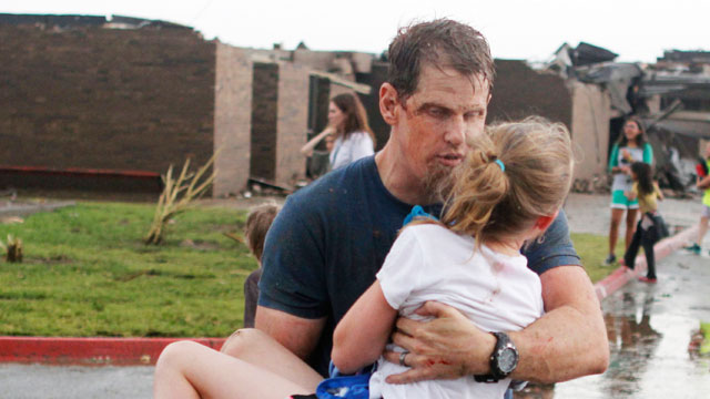 PHOTO: Teachers carry children away from Briarwood Elementary school after a tornado destroyed the school in south Oklahoma City, May 20, 2013.