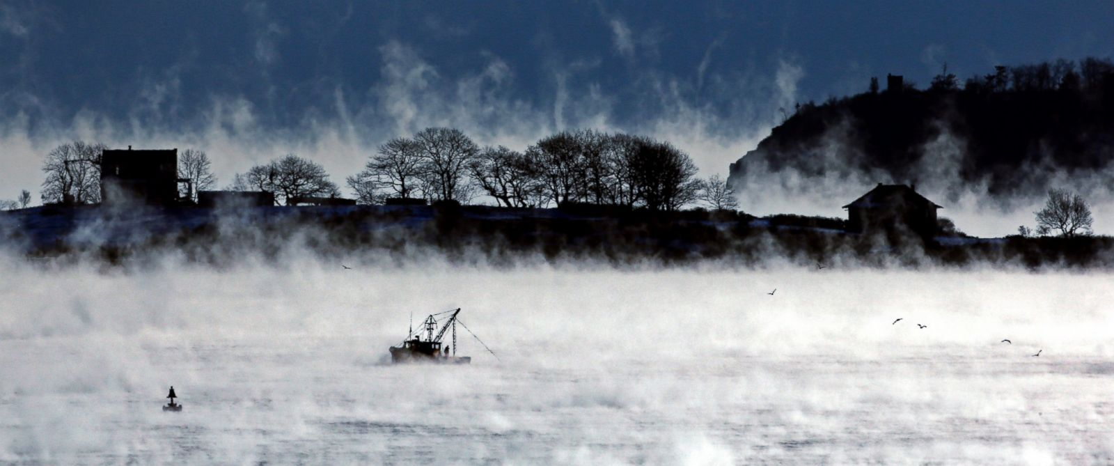 PHOTO: A fisherman works aboard a trawler passing House Island in Casco Bay of Portland, Maine, where the temperature at dawn was minus-9 degrees on Jan. 8, 2014.